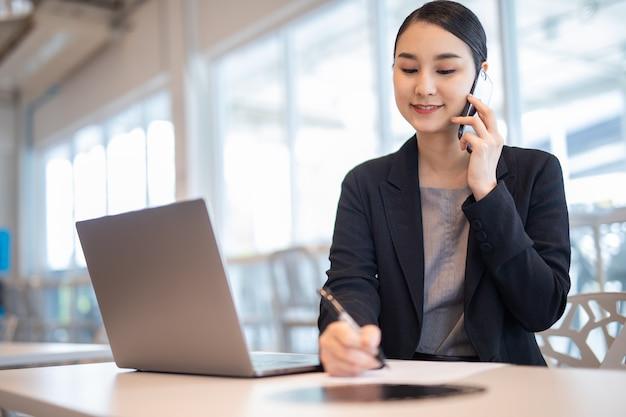 Mujer asiática que trabaja en una oficina moderna con una computadora portátil