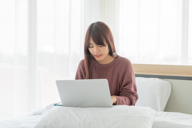 Mujer asiática que trabaja con el portátil en la cama