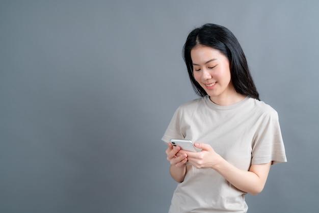Mujer asiática que usa aplicaciones de teléfonos móviles, disfruta de la comunicación a distancia en línea en una red social o de compras aisladas en la pared gris