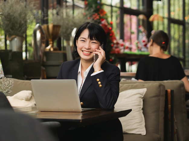Mujer asiática que usa la computadora portátil y tomando café en la cafetería cafetería