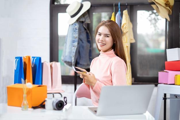 Mujer asiática que usa la computadora y sonriendo mientras está sentado en el taller