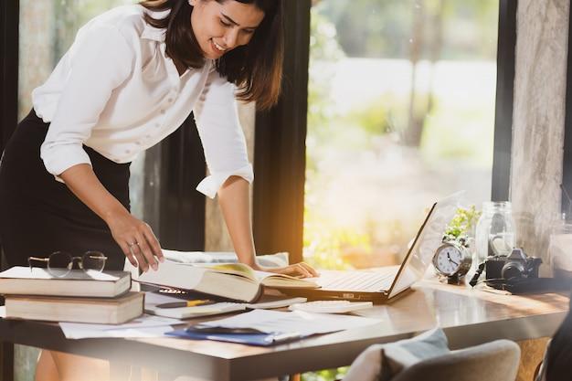 Mujer asiática que usa el ordenador portátil que trabaja con feliz.