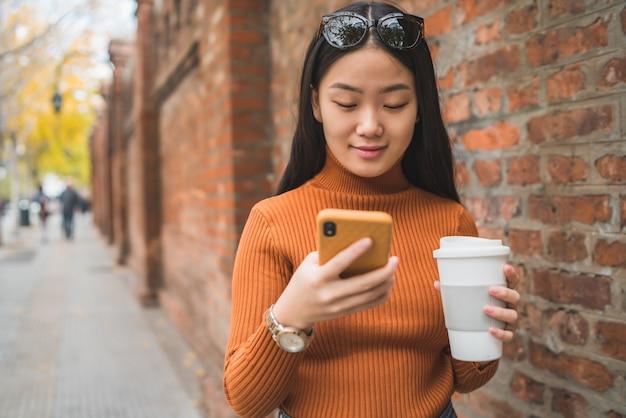 Mujer asiática que usa su teléfono móvil