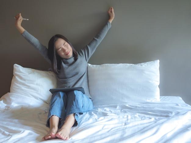 Mujer asiática que usa la tableta en la cama