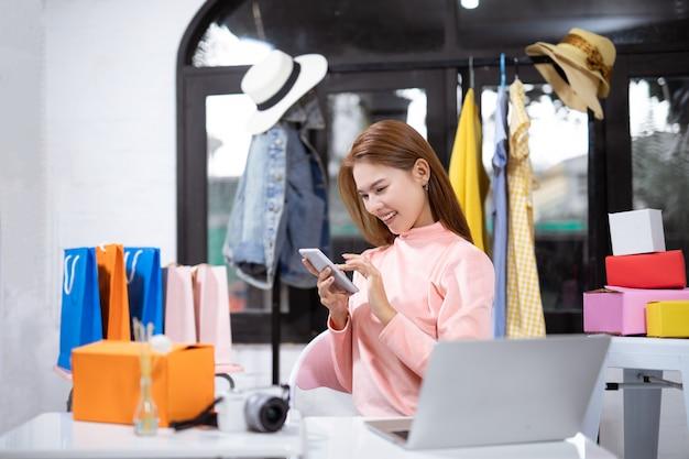 Mujer asiática que usa un teléfono inteligente y sonriendo mientras está sentado en el taller