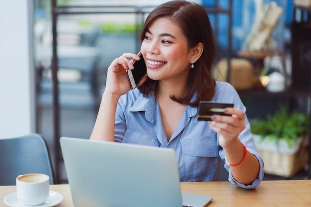 Mujer asiática que usa el teléfono móvil con tarjeta de crédito y computadora portátil para comprar pagos en línea en la cafetería cafetería con amigos