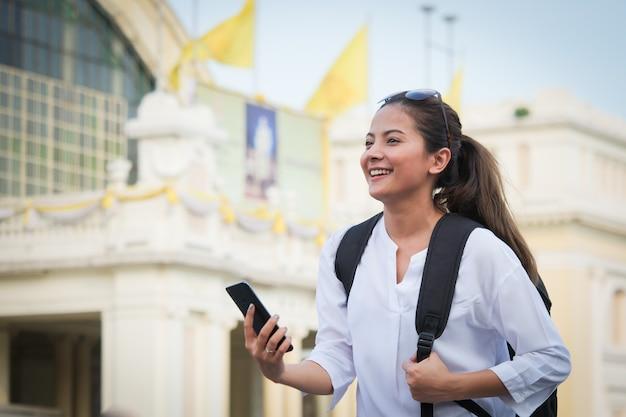 Mujer asiática que viaja con teléfono móvil