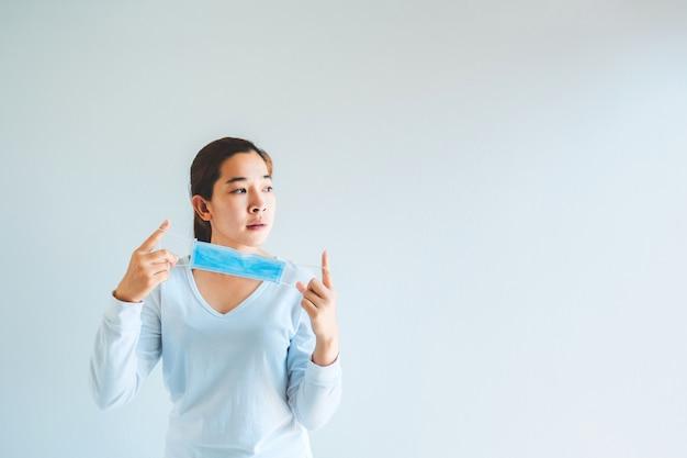 Mujer asiática quitándose su máscara de protección