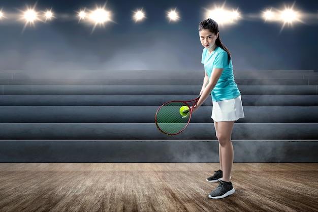 Mujer asiática con una raqueta de tenis y pelota en sus manos listo en posición de servicio