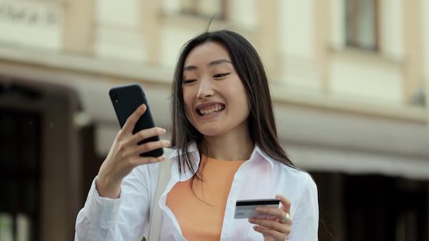 Mujer asiática realiza pagos en línea a través de internet desde tarjeta bancaria en smartphone chica estudiante en la calle con tarjeta de crédito y teléfono mujer celebrando una compra exitosa