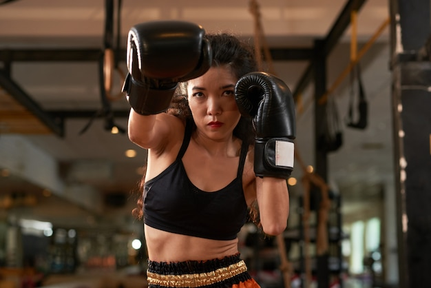 Mujer asiática recortada entrenando en guantes de boxeo en la práctica de muay thai
