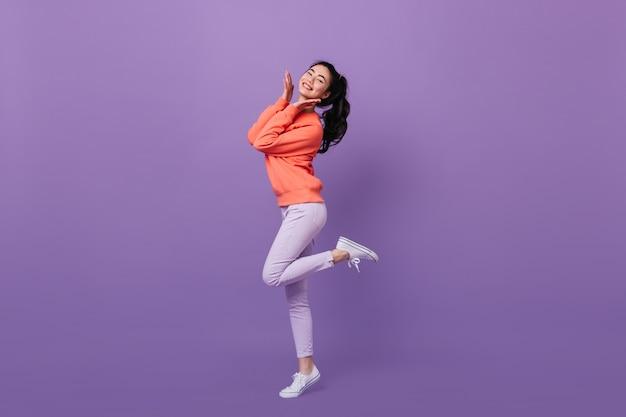 Mujer asiática refinada de pie sobre una pierna. vista de longitud completa de la mujer china dichosa bailando sobre fondo púrpura.