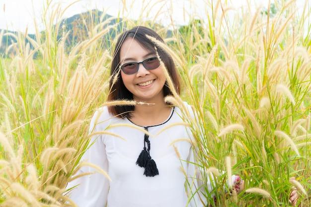 La mujer asiática se relaja en campo de hierba.