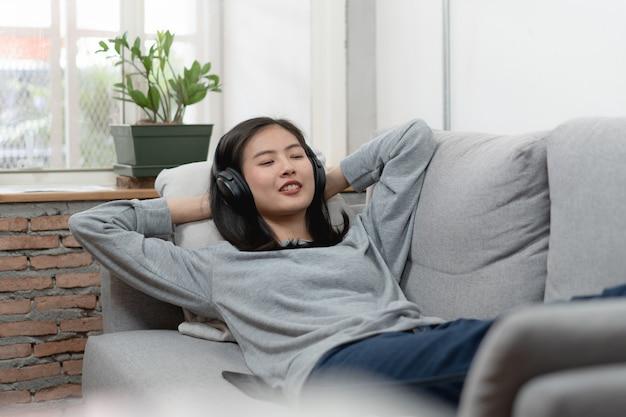 Mujer asiática relajada en música que escucha de los auriculares y que coloca en el sofá.