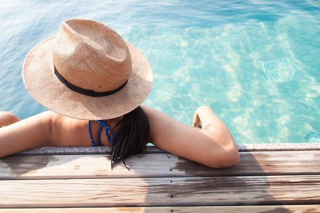 Mujer asiática relajante en piscina, concepto de vacaciones de viaje
