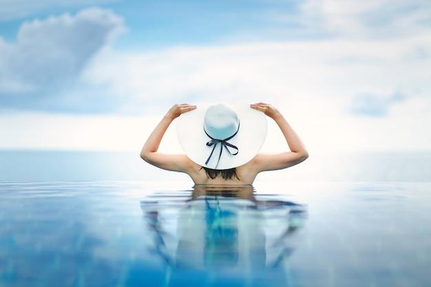 Mujer asiática relajarse en la piscina en la playa