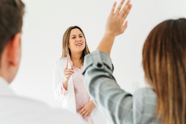 Mujer asiática respondiendo preguntas de compañeros de trabajo