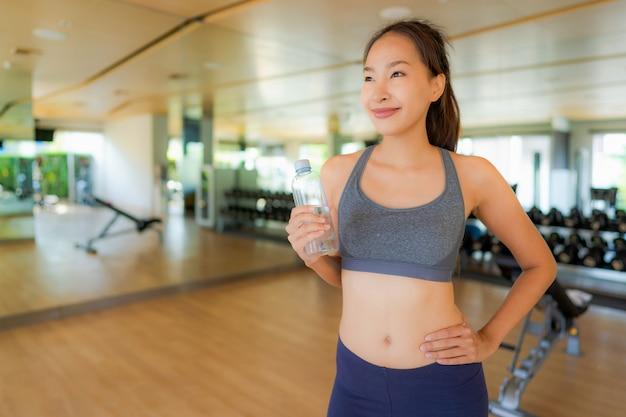 Mujer asiática del retrato que come el agua en gimnasio