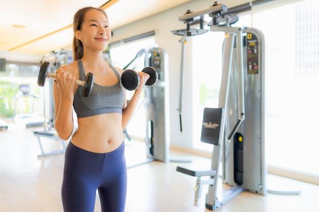 La mujer asiática del retrato que ejercita y se resuelve en gimnasio