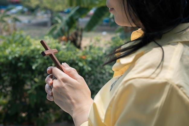 Mujer asiática rezando con cruz de madera al aire libre.