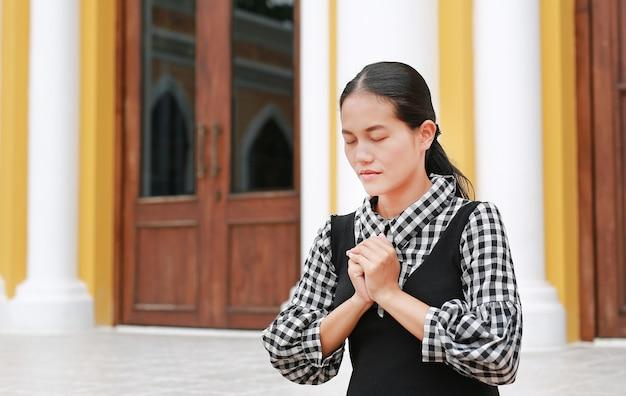 Mujer asiática rezando en la iglesia