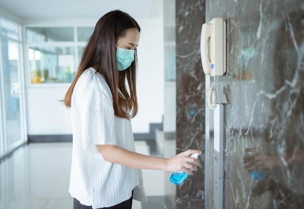 Mujer asiática rociando alcohol, usando un botón de elevador matar gérmenes y virus