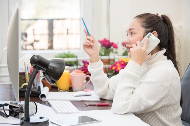 Mujer asiática en ropa casual está trabajando con teléfono y computadora portátil para comunicarse en internet con clientes en la habitación