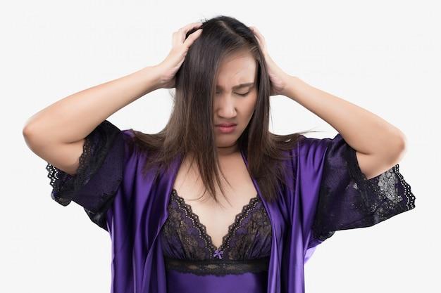 Mujer asiática en ropa de dormir de satén y túnica púrpura que sufre de dolor de cabeza en la noche.