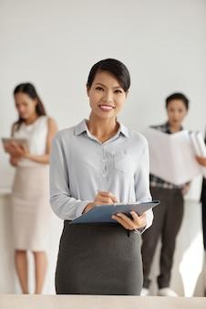 Mujer asiática en ropa elegante posando en estudio con portapapeles y colegas en segundo plano.