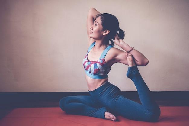 Mujer asiática sana y feliz practicando yoga, pose de una paloma rey en el hogar, estilo de vida de bienestar y fitness