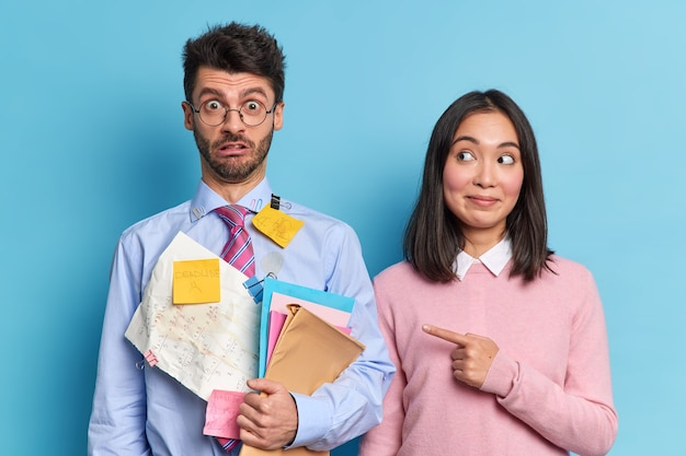 Una mujer asiática satisfecha señala a su compañera de grupo, que tiene una expresión muy sorprendida y se da cuenta de que tiene una fecha límite para prepararse para la sesión atascada con notas adhesivas para los exámenes. dos estudiantes diversos en el interior.