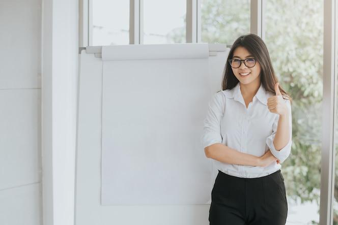 Mujer asiática segura con rotafolio en blanco