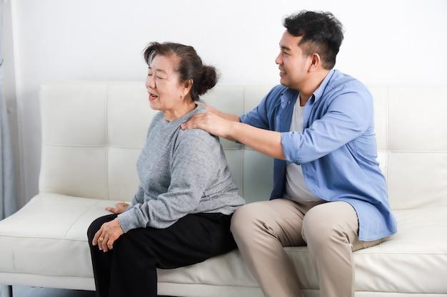 Mujer asiática senior madre e hijo joven en camisa azul masajear a su madre en la sala de estar