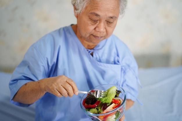 Mujer asiática de la señora que sostiene el alimento sano.