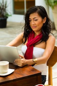 Mujer asiática está sentada en un bar o cafetería al aire libre