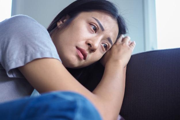 Mujer asiática sentada dentro de la casa mirando por la ventana