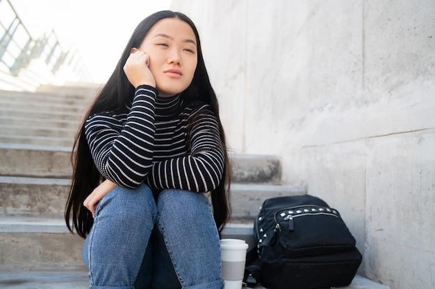 Mujer asiática sentada en las escaleras de hormigón.