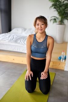 Mujer asiática sentada en la estera, está a punto de entrenar en casa, vistiendo ropa deportiva