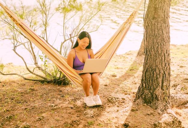Mujer asiática sentada en hamaca con laptop y sonriendo