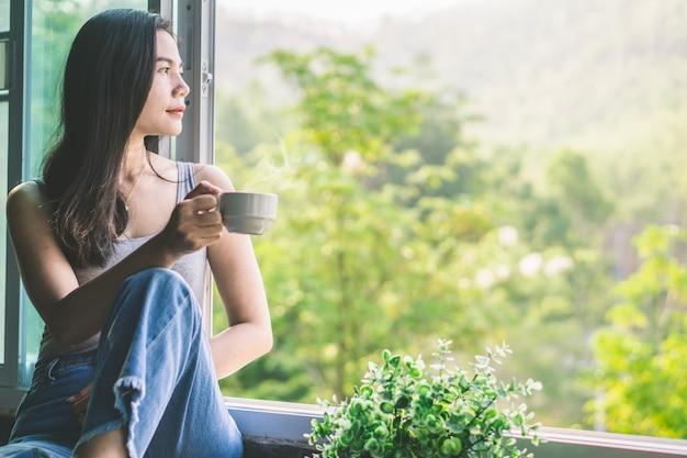 Mujer asiática sentada junto a la ventana tomando café