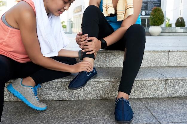 Mujer asiática sentada en pasos en la calle y sosteniendo el tobillo de un amigo