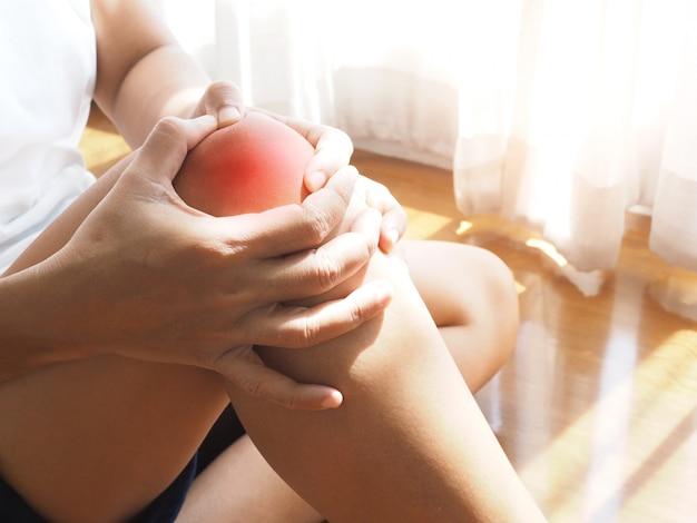 Mujer asiática sentada en el piso con dolor de rodilla y utilizando masaje de manos para relajarse.