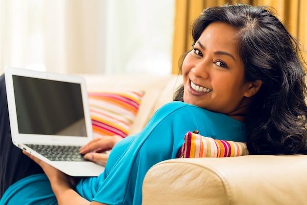 Mujer asiática sentada en el sofá navegando por internet y sonriendo