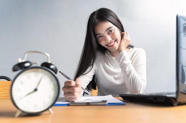 Mujer asiática sentada y trabajando en casa o reunión en línea, video conferencia y escribir datos en un libro en la oficina en casa.