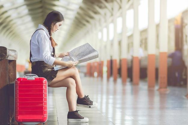 La mujer asiática se sienta en el banco mira el mapa con la maleta roja en la estación de tren de viaje