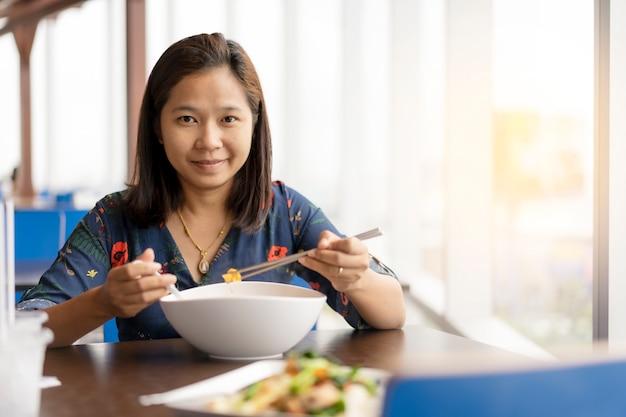 La mujer asiática se sienta cerca de la ventana y disfruta feliz con la comida de fideos chinos.