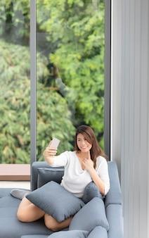 La mujer asiática se sienta en el sofá con el móvil