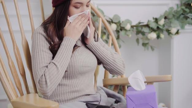 Mujer asiática siente dolor de cabeza envuelto en una manta gris, se sopla la nariz y usa tejido