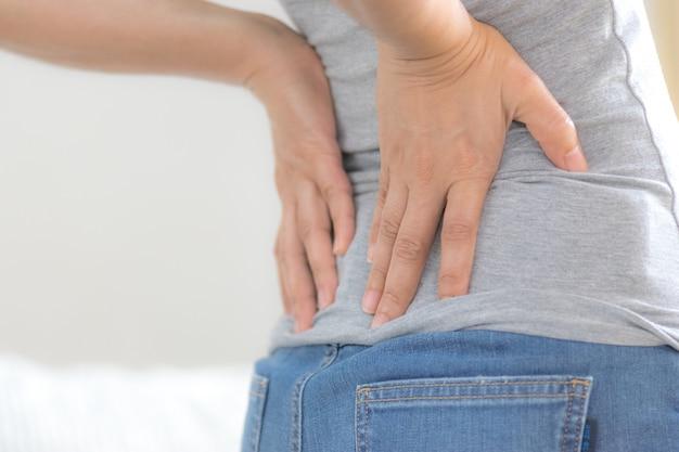 Mujer asiática siente dolor en la espalda y la cadera, sintiéndose mal en la sala de estar. concepto sanitario y médico.