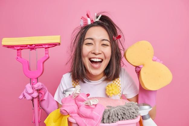 La mujer asiática sincera positiva con cepillo de limpieza y pinzas para la ropa en el cabello sonríe ampliamente se siente feliz por hacer las tareas del hogar